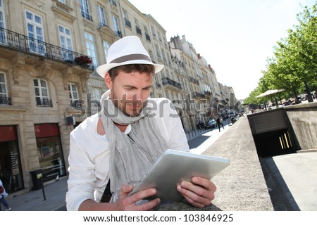 Young man with hat in town using electronic tablet - stock photo