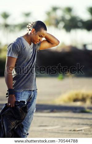 Young man with head down looking sad - stock photo