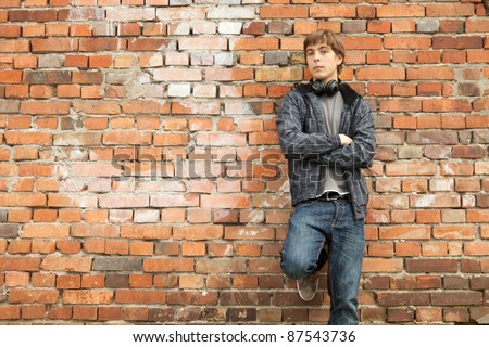 young man with headphones leaning on the old, bricks wall