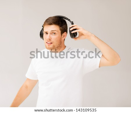 young man with headphones listening loud music - stock photo