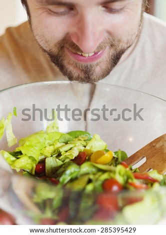 Young man with healthy colorful vegetable salad