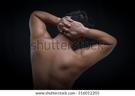 young man with his arms stretched out isolated on black background - stock photo