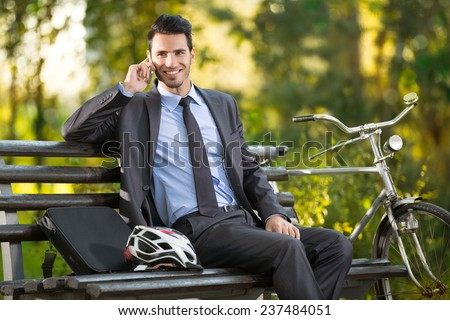 young man with his bicycle talking and resting in park  - stock photo