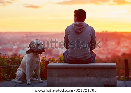 Young man with his dog at the sunrise. - stock photo