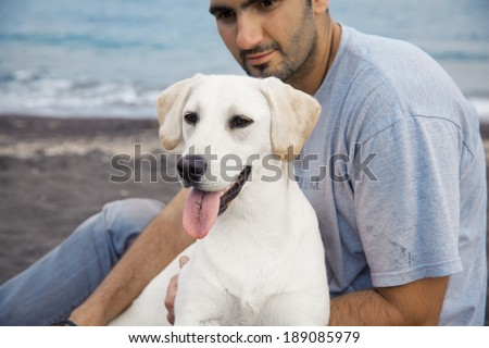 young man with his dog on the beach. horizontal shot - stock photo