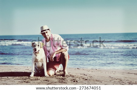 Young man with his dog on the beach with the sea in the background - stock photo
