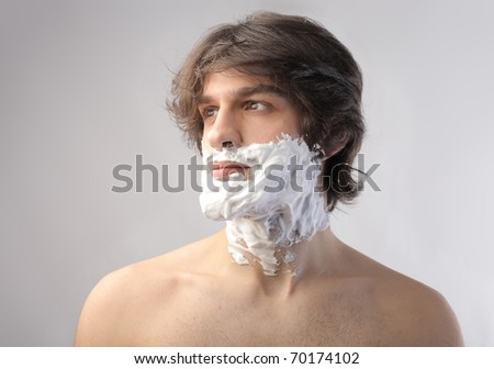 Young man with his face full of shaving cream - stock photo
