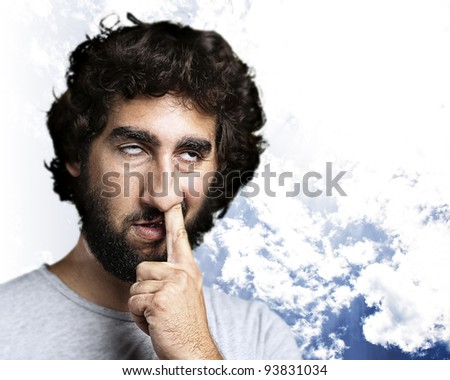 young man with his finger in his nose against a cloudy sky background - stock photo