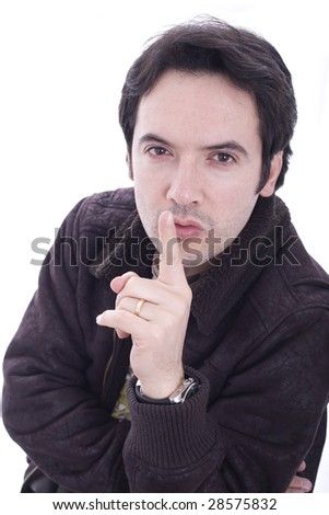 Young man with his finger on his lips - stock photo