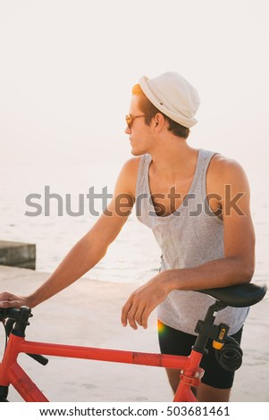 Young man with his fixed gear bike on seafront during sunset or sunrise
