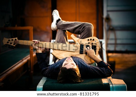 young man with his guitar, outdoor shot - stock photo