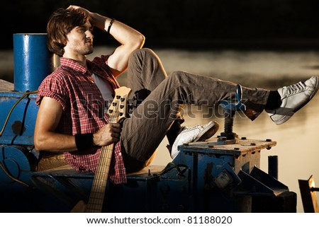 young man with his guitar relaxing by the river, sunset, full body shot