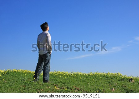 Young man with his hand on the pocket enjoying the nature - stock photo