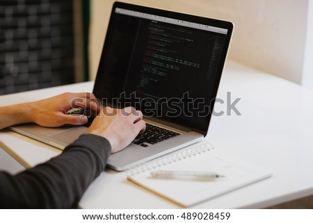 Young man with his laptop in the room. Man searching the web at the wooden table. Laptop screen with code elements on it. Notebook and pen with web elements and ideas written. Concept of web page