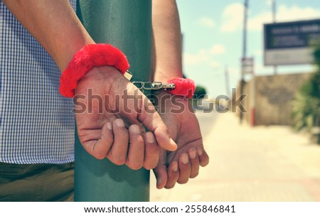young man with his wrists locked in the back in a streetlight with sexy fluffy handcuffs - stock photo