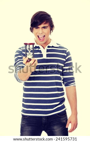Young man with hourglass in hand - stock photo
