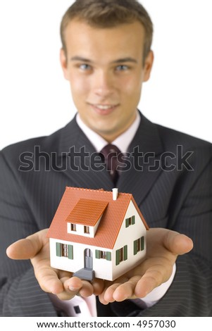 Young man with house miniature in hands. Smiling and looking at camera. White background, front view. Focus on miniature - stock photo