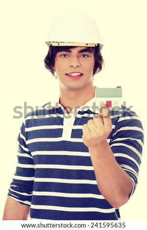Young man with house model. - stock photo