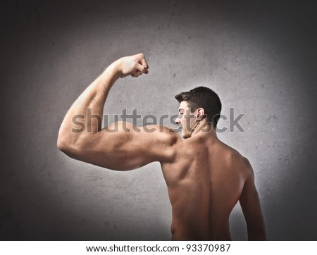 Young man with huge muscular arm - stock photo
