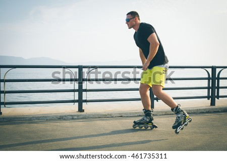 young man with inline skates ride in summer park seafront outdoor roller skater