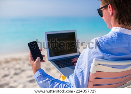 Young man with laptop and cell phone on tropical beach - stock photo