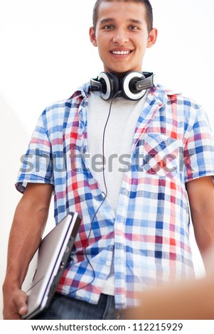 Young man with laptop and headphones - stock photo