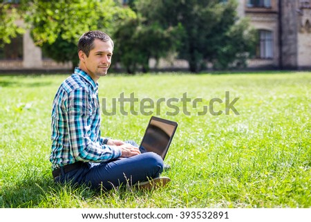 Young man with laptop enjoing working in the park