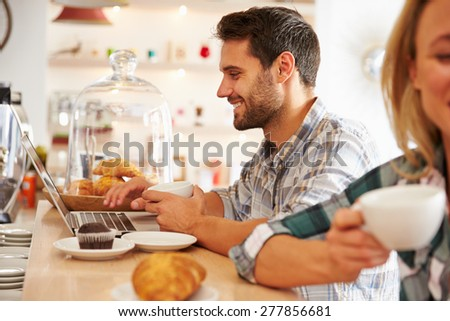 Young man with laptop in a cafe - stock photo