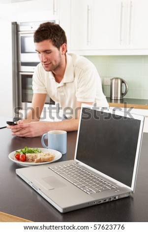Young Man With Laptop In Modern Kitchen About To Eat Meal - stock photo