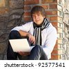 Young man with laptop leaning against the brick wall - stock