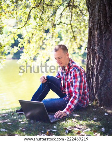 Young man with laptop near lake in city park outdoor. Caucasian man sitting on green grass and working on his laptop  - stock photo