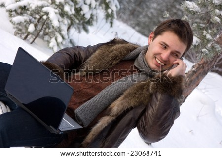 young man with laptop outdoors talking mobile phone - stock photo