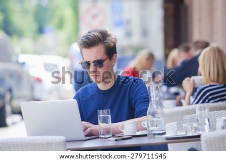 Young Man with Laptop Sitting in Outside Coffeehouse Working