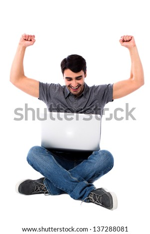 Young man with laptop sitting on floor, raising hands in excitement. - stock photo