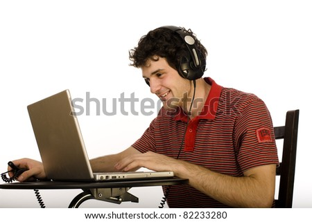 Young man with laptop wearing earphones - stock photo