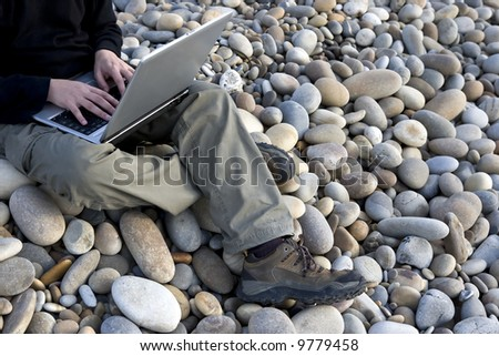 young man with laptop working outdoors - stock photo