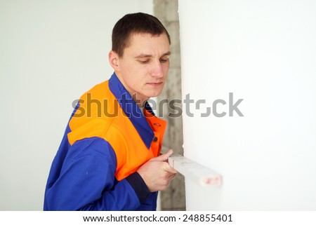 Young man with level - stock photo