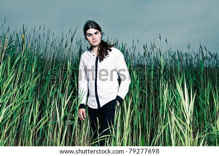 Young man with long brown hair standing in field with long grass. Stormy cloudy sky.