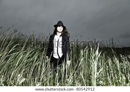 Young man with long brown hair wearing black suit and black hat standing in field with long grass. Stormy cloudy sky. - stock photo