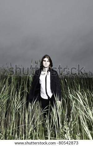 Young man with long brown hair wearing black suit standing in field with long grass. Stormy cloudy sky.