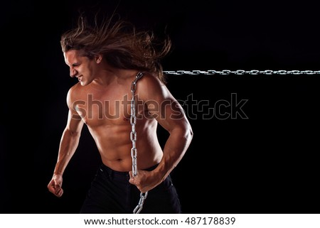 Young man with long hair dragging something behind him. Strong.