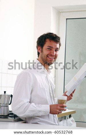 young man with magazine drinking coffee