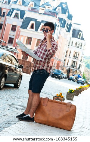 Young man with map and suitcase standing on side of street. - stock photo