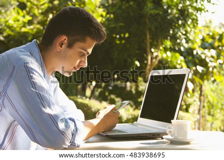 young man with mobile and laptop