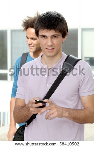 young man with mobile phone at college campus