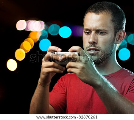 young man with mobile phone at shopping center by night - stock photo