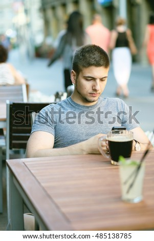 Young man with mobile phone in outdoor restaurant