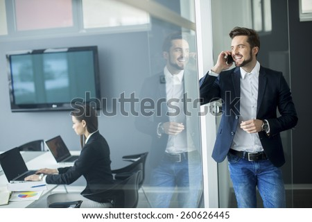 Young man with mobile phone in the office - stock photo