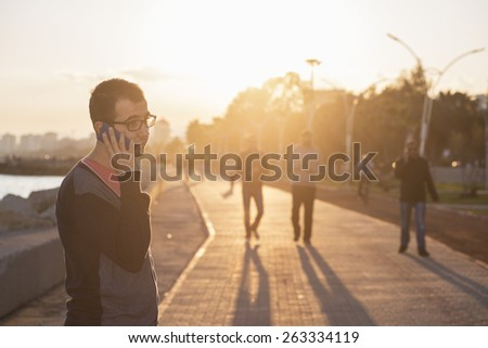 Young Man with mobile phone walking. - stock photo