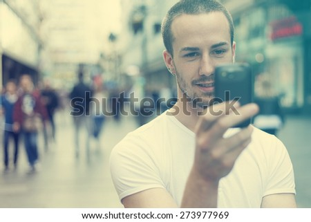 Young Man with mobile phone walking, background is blurred city - stock photo